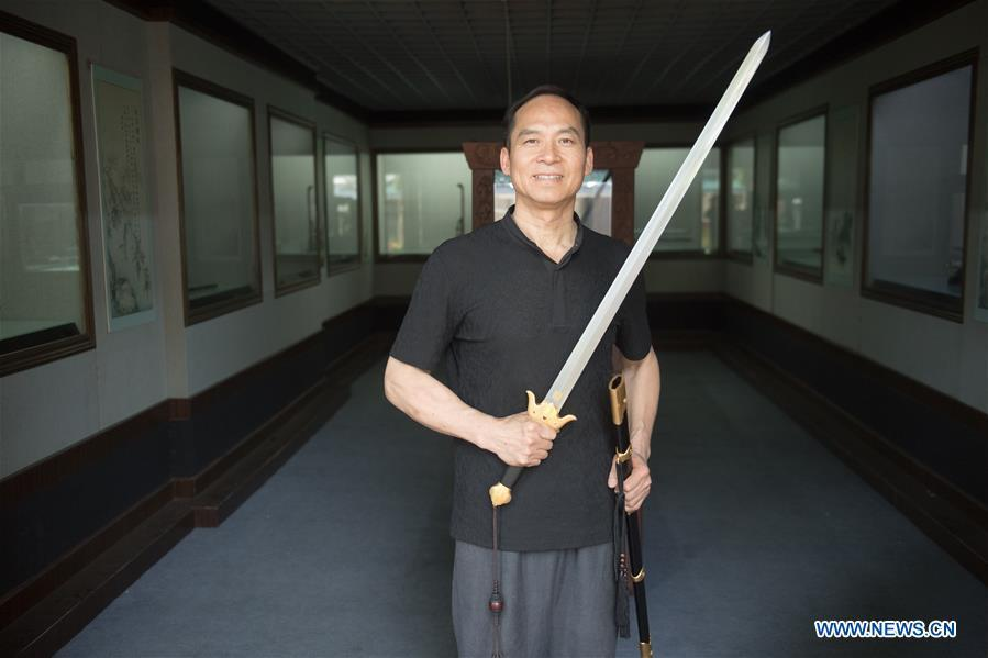 Zheng Guorong poses for a photo with a sword he made at Guyue Sword Studio in Longquan, east China\'s Zhejiang Province, May 21, 2019. For centuries, Longquan has been famed for its sword making industry. Zheng Guorong, 55, an intangible cultural heritage inheritor in Longquan Sword making, has been making sword for more than 30 years. Zheng regards sword as a symbol of spirit and devotes all to his career with awe. In his studio, the whole process of making a single sword takes two to three months, with steps including forming an idea, designing the sketch, preparing material and the final making and assembling. After setting up his studio, Zheng has trained more than 20 apprentices, who have all become sword smiths of great reputation. The old sword smith insists that Longquan sword, with a history of more than 2,500 years, deserves to be carried on in our time, both materially and spiritually. (Xinhua/Weng Xinyang)