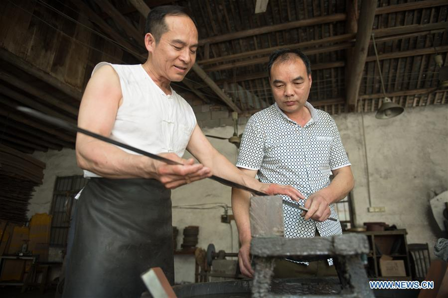 Zheng Guorong (L) and his co-worker Wu Changyou discuss sword burnishing skills at Guyue Sword Studio in Longquan, east China\'s Zhejiang Province, May 21, 2019. For centuries, Longquan has been famed for its sword making industry. Zheng Guorong, 55, an intangible cultural heritage inheritor in Longquan Sword making, has been making sword for more than 30 years. Zheng regards sword as a symbol of spirit and devotes all to his career with awe. In his studio, the whole process of making a single sword takes two to three months, with steps including forming an idea, designing the sketch, preparing material and the final making and assembling. After setting up his studio, Zheng has trained more than 20 apprentices, who have all become sword smiths of great reputation. The old sword smith insists that Longquan sword, with a history of more than 2,500 years, deserves to be carried on in our time, both materially and spiritually. (Xinhua/Weng Xinyang)