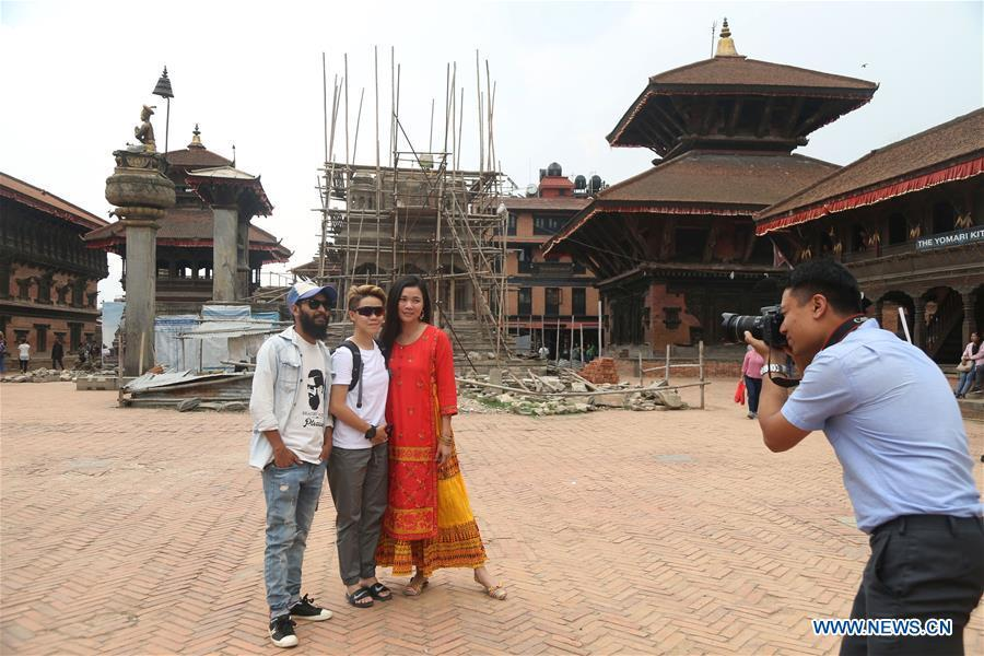 Binaya Hada (R) takes picture of tourists at Bhaktapur Durbar Square in Bhaktapur, Nepal on May 15, 2019. Binaya Hada is a 34-year-old Nepali young man, whose work was selected for a photographic exhibition on Asian civilization. Graduated from Beijing Language and Culture University of China, Binaya is now dedicated to learning Chinese culture and popularizing knowledge of Chinese language to local population. (Xinhua/Sunil Sharma)