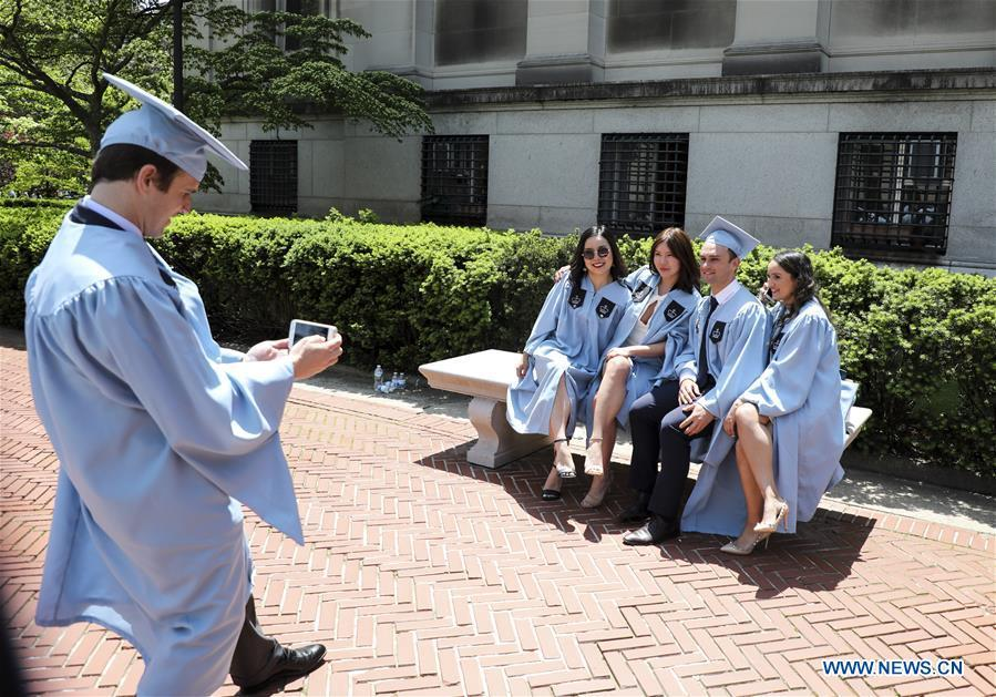 Graduate students pose for photos on campus after the Columbia University Commencement ceremony in New York, the United States, May 22, 2019. The Columbia University Commencement ceremony of the 265th academic year took place on Wednesday. More than 17,000 students from Columbia\'s 18 schools and affiliates graduated this year. (Xinhua/Wang Ying)