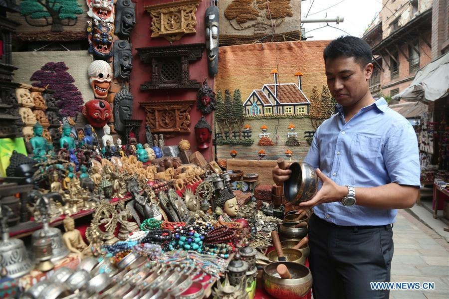 Binaya Hada buys gifts for his Chinese friends at a shop in Bhaktapur, Nepal on May 15, 2019. Binaya Hada is a 34-year-old Nepali young man, whose work was selected for a photographic exhibition on Asian civilization. Graduated from Beijing Language and Culture University of China, Binaya is now dedicated to learning Chinese culture and popularizing knowledge of Chinese language to local population. (Xinhua/Sunil Sharma)