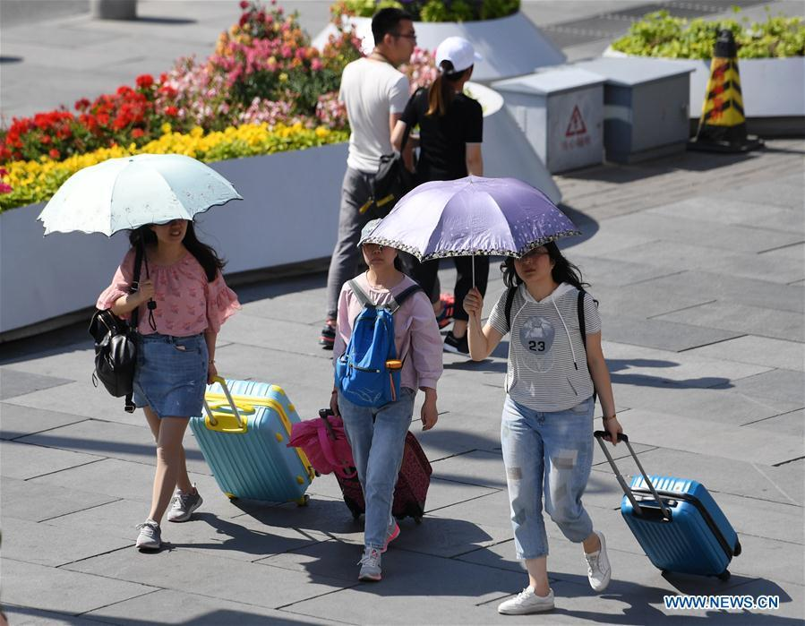 Pedestrians hold umbrellas as sun shade in Beijing, capital of China, May 22, 2019. Beijing\'s observatory issued a yellow alert on Tuesday for high temperatures over the next four days. Temperature could rise to 35 degrees Celsius from Wednesday to Saturday, and reach up to 37 degrees Celsius on Thursday. (Xinhua/Zhang Chenlin)