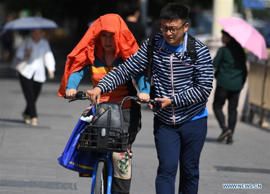 A pedestrian (L) puts a jacket over her head and shoulders as sun shade in Beijing, capital of China, May 22, 2019. Beijing\'s observatory issued a yellow alert on Tuesday for high temperatures over the next four days. Temperature could rise to 35 degrees Celsius from Wednesday to Saturday, and reach up to 37 degrees Celsius on Thursday. (Xinhua/Zhang Chenlin)