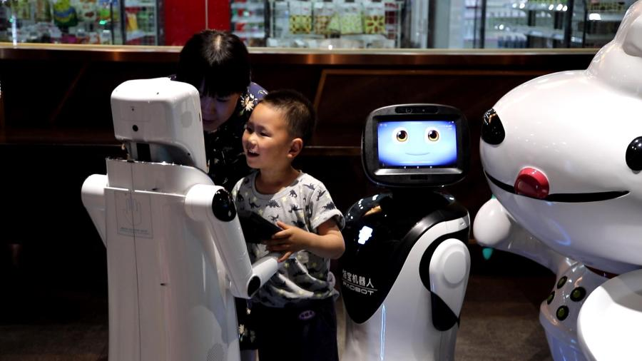 A child chats with an AI robot at the X Future Restaurant.  (Photo/People\'s Daily Online)