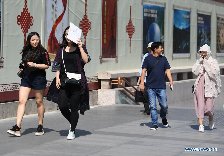 A pedestrian (2nd L) uses a personal item as sun shade in Beijing, capital of China, Beijing\'s observatory issued a yellow alert on Tuesday for high temperatures over the next four days. Temperature could rise to 35 degrees Celsius from Wednesday to Saturday, and reach up to 37 degrees Celsius on Thursday. (Xinhua/Zhang Chenlin)