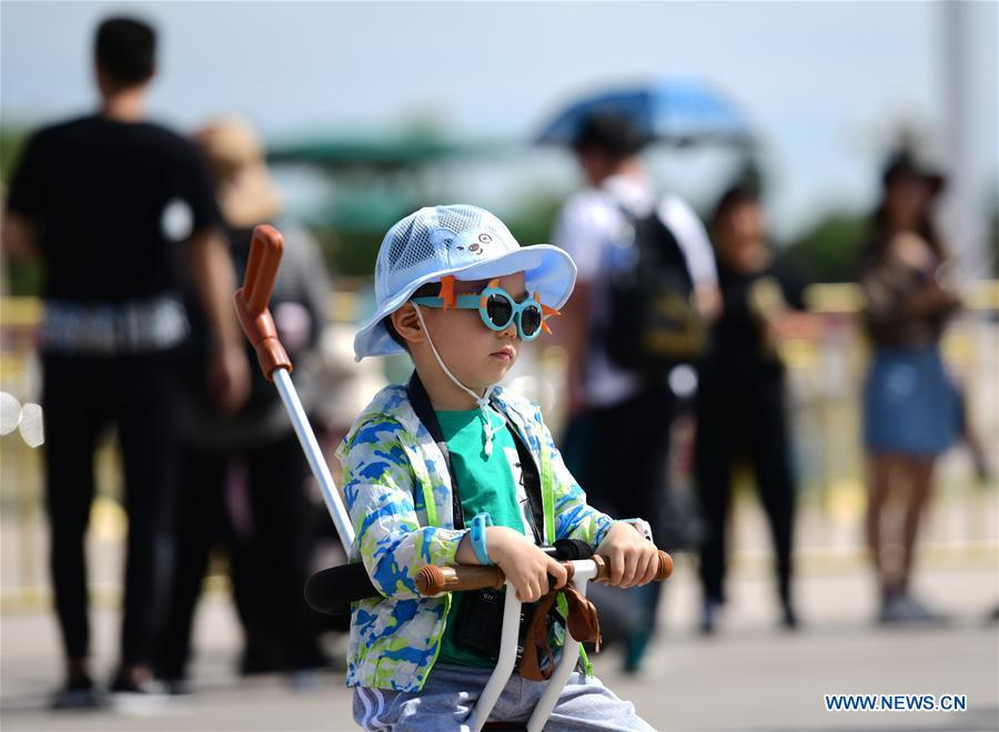 A child wears sunglasses as protection against sunlight in Beijing, capital of China, May 22, 2019. Beijing\'s observatory issued a yellow alert on Tuesday for high temperatures over the next four days. Temperature could rise to 35 degrees Celsius from Wednesday to Saturday, and reach up to 37 degrees Celsius on Thursday. (Xinhua/Zhang Chenlin)