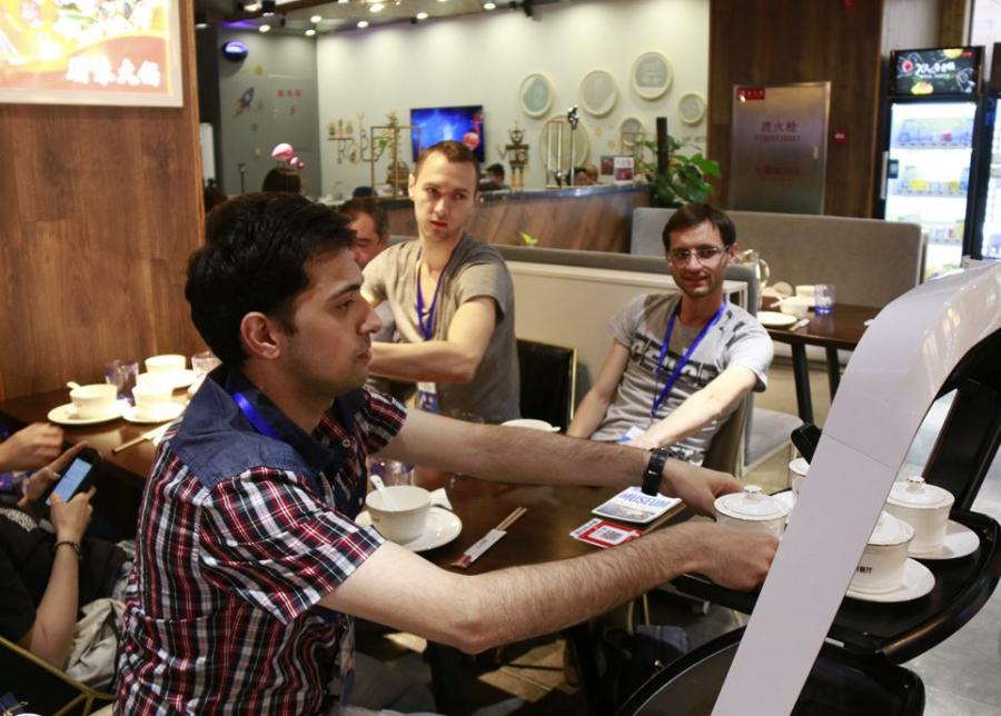A customer takes food from a robot at the X Future Restaurant. (Photo/People\'s Daily Online)