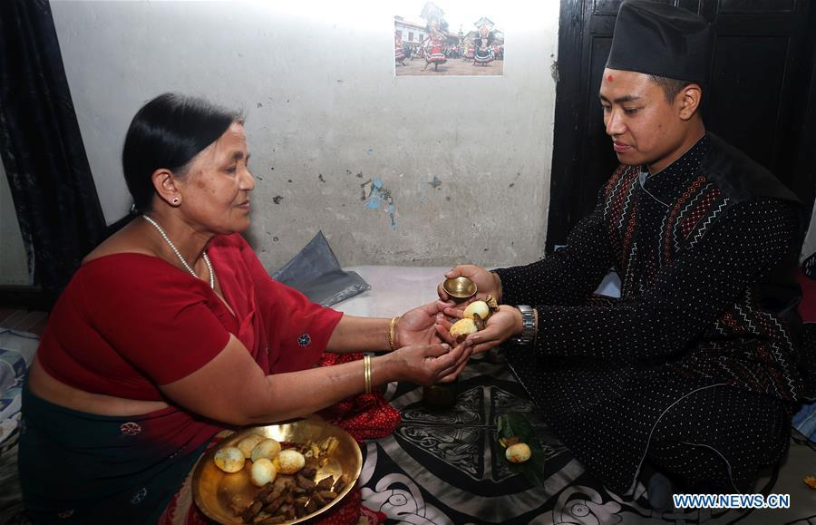Binaya Hada (R) receives blessings from his mother at home in Bhaktapur, Nepal on May 15, 2019. Binaya Hada is a 34-year-old Nepali young man, whose work was selected for a photographic exhibition on Asian civilization. Graduated from Beijing Language and Culture University of China, Binaya is now dedicated to learning Chinese culture and popularizing knowledge of Chinese language to local population. (Xinhua/Sunil Sharma)