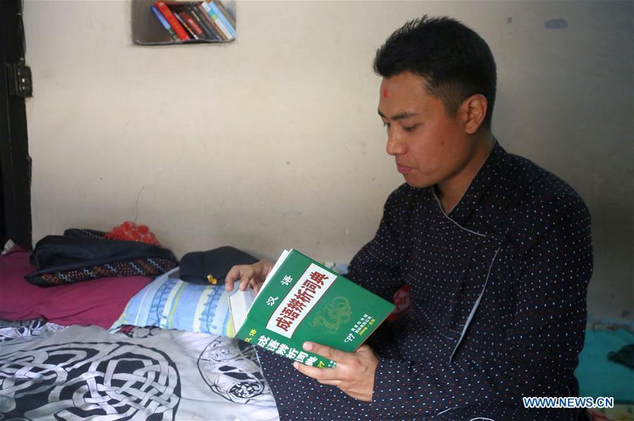 Binaya Hada reads a Chines book at his home in Bhaktapur, Nepal on May 15, 2019. Binaya Hada is a 34-year-old Nepali young man, whose work was selected for a photographic exhibition on Asian civilization. Graduated from Beijing Language and Culture University of China, Binaya is now dedicated to learning Chinese culture and popularizing knowledge of Chinese language to local population. (Xinhua/Sunil Sharma)