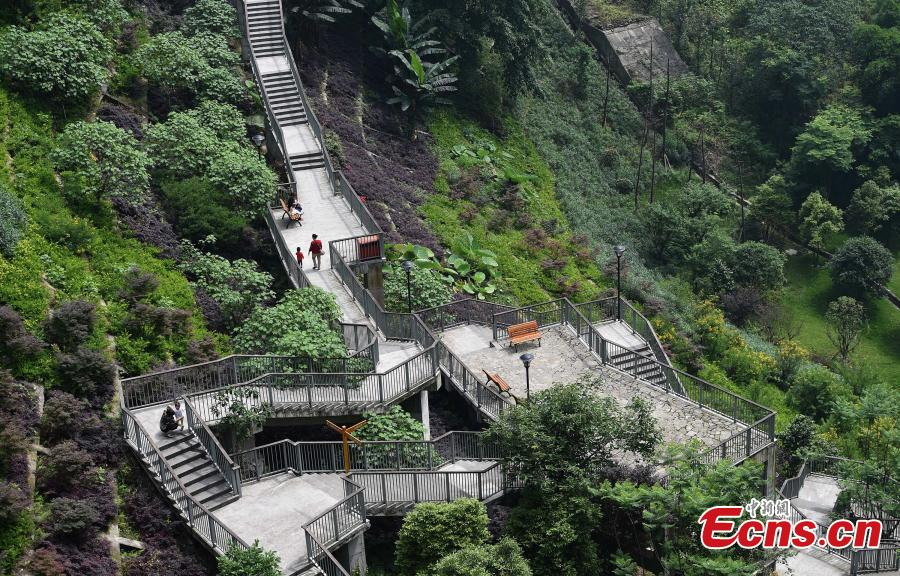 A view of a pathway built along a hilly slope leading to the entrance of a residential community in Yuzhong District, Southwest China's Chongqing Municipality, May 22, 2019. The road is about one kilometre long, with a height of nearly 100 meters. Built on mountains, the city has been nicknamed a \
