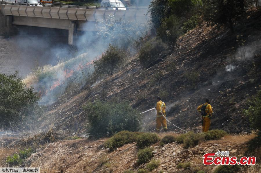 Firefighters extinguish a fire in a forest amidst extreme heat wave near the Israeli city of Modiin on May 23, 2019. (Photo/Agencies)
