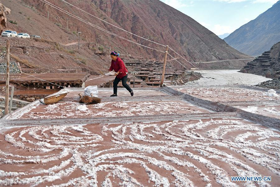 A villager collects salt at a saline field in Mangkam County, southwest China\'s Tibet Autonomous Region, May 22, 2019. An ancient technique of salt production since Tang Dynasty (618-907) is well-preserved in Mangkam County. Local people follow a salt harvesting method by collecting brines from salt mines and ponds and evaporating them in the sun until crystallization. (Xinhua/Li Xin)
