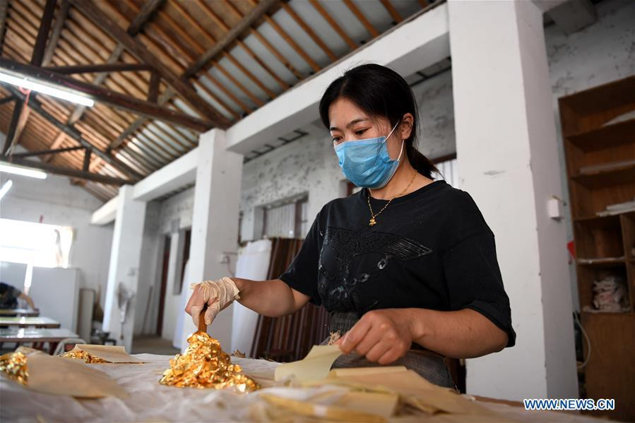 A worker prepares sheets of gold foil before grinding them into powder to make Fenlajian paper at a workshop run by paper artisan Liu Jing in Huanglu Township of Chaohu, east China\'s Anhui Province, May 23, 2019. Fenlajian is a high-end wax mineral paper which dates back to the Tang dynasty (618-907). For centuries, access to the Fenlajian paper had remained a privilege reserved solely for China\'s imperial families, due to the costly materials and the set of complicated procedures involved in its making. The techniques in producing this fine writing and painting material even became lost in the late Qing dynasty (1644-1911), until Liu Jing, an Anhui-based paper artisan, managed to revive them through constant trials by the end of the 20th century. Born in a family of paper-makers, Liu now runs a paper workshop dedicated to making Fenlajian and other classical papers while promoting their know-hows. Liu\'s classical paper processing techniques were listed as a national intangible cultural heritage in 2008, and he himself was named as a national representative inheritor to the aforementioned techniques in 2018. (Xinhua/Liu Junxi)