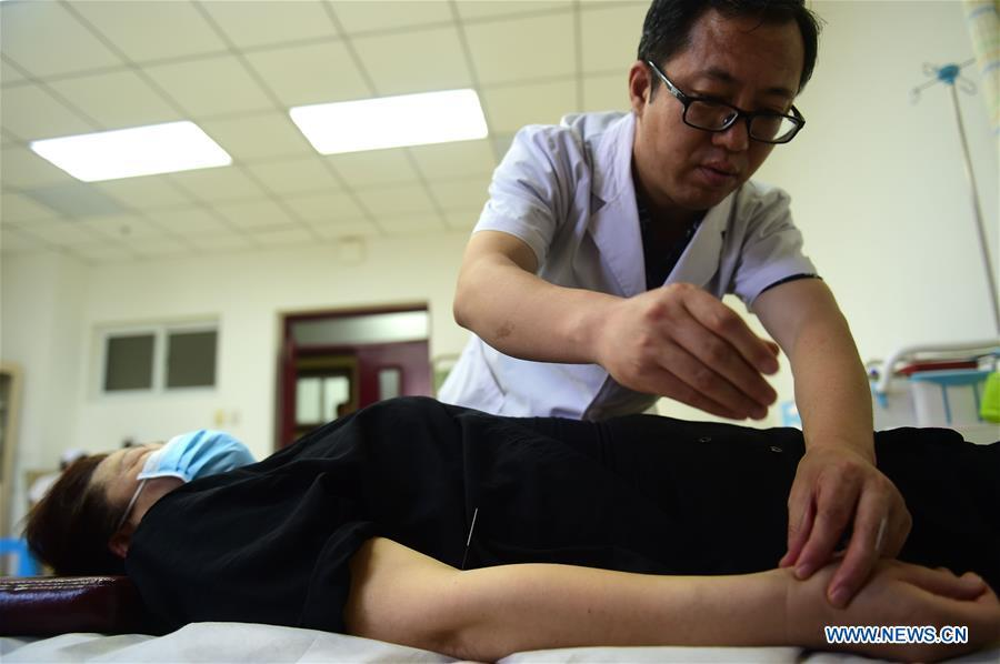 A doctor gives acupuncture treatment to a patient at Cangzhou People\'s Hospital in Cangzhou, north China\'s Hebei Province, May 26, 2019. Traditional medicine originating from Traditional Chinese Medicine (TCM) has been incorporated into the 11th revision of the International Classification of Diseases (ICD), marking a major step for TCM\'s internationalization. The revision was approved Saturday at the 72 World Health Assembly being held in Geneva, Switzerland, according to China\'s National Administration of Traditional Chinese Medicine. (Xinhua/Fu Xinchun)