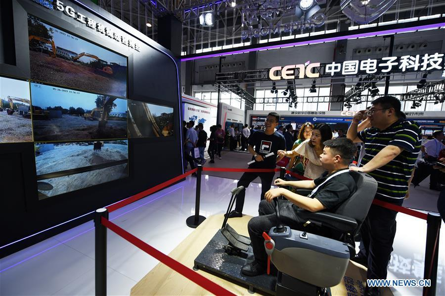 A visitor operates an excavator by a remote control system via 5G technology during China International Big Data Industry Expo 2019 in Guiyang, southwest China\'s Guizhou Province, May 26, 2019. The expo on big data opened Sunday in Guizhou Province, focusing on the latest innovation of the technology and its applications. The four-day expo will be attended by 448 enterprises from 59 countries and regions, according to the organizing committee. (Xinhua/Yang Wenbin)