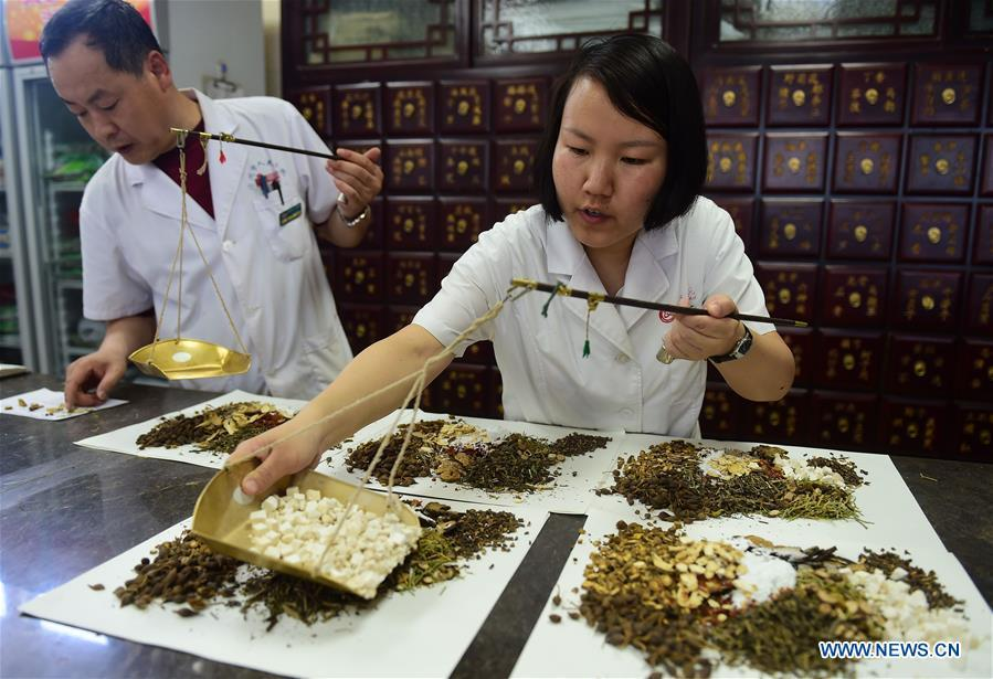 Staff members of Cangzhou People\'s Hospital fill prescriptions of Traditional Chinese Medicine for patients in Cangzhou, north China\'s Hebei Province, May 26, 2019. Traditional medicine originating from Traditional Chinese Medicine (TCM) has been incorporated into the 11th revision of the International Classification of Diseases (ICD), marking a major step for TCM\'s internationalization. The revision was approved Saturday at the 72 World Health Assembly being held in Geneva, Switzerland, according to China\'s National Administration of Traditional Chinese Medicine. (Xinhua/Fu Xinchun)