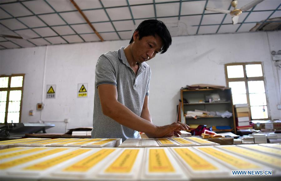 A worker wraps up Fenlajian paper products at a workshop run by paper artisan Liu Jing in Huanglu Township of Chaohu, east China\'s Anhui Province, May 23, 2019. Fenlajian is a high-end wax mineral paper which dates back to the Tang dynasty (618-907). For centuries, access to the Fenlajian paper had remained a privilege reserved solely for China\'s imperial families, due to the costly materials and the set of complicated procedures involved in its making. The techniques in producing this fine writing and painting material even became lost in the late Qing dynasty (1644-1911), until Liu Jing, an Anhui-based paper artisan, managed to revive them through constant trials by the end of the 20th century. Born in a family of paper-makers, Liu now runs a paper workshop dedicated to making Fenlajian and other classical papers while promoting their know-hows. Liu\'s classical paper processing techniques were listed as a national intangible cultural heritage in 2008, and he himself was named as a national representative inheritor to the aforementioned techniques in 2018. (Xinhua/Liu Junxi)