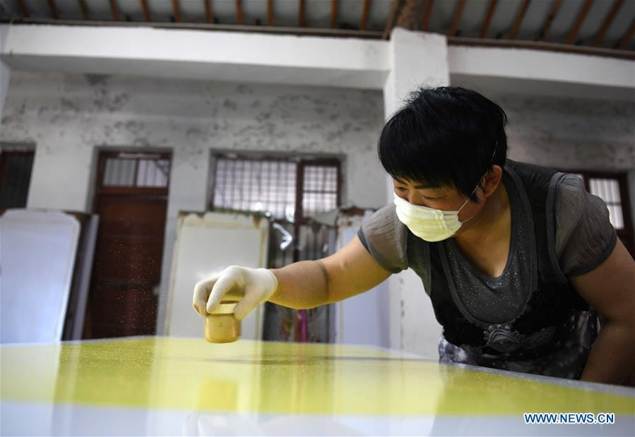 A worker scatters gold powder onto a piece of Fenlajian paper at a workshop run by paper artisan Liu Jing in Huanglu Township of Chaohu, east China\'s Anhui Province, May 23, 2019. Fenlajian is a high-end wax mineral paper which dates back to the Tang dynasty (618-907). For centuries, access to the Fenlajian paper had remained a privilege reserved solely for China\'s imperial families, due to the costly materials and the set of complicated procedures involved in its making. The techniques in producing this fine writing and painting material even became lost in the late Qing dynasty (1644-1911), until Liu Jing, an Anhui-based paper artisan, managed to revive them through constant trials by the end of the 20th century. Born in a family of paper-makers, Liu now runs a paper workshop dedicated to making Fenlajian and other classical papers while promoting their know-hows. Liu\'s classical paper processing techniques were listed as a national intangible cultural heritage in 2008, and he himself was named as a national representative inheritor to the aforementioned techniques in 2018. (Xinhua/Liu Junxi)