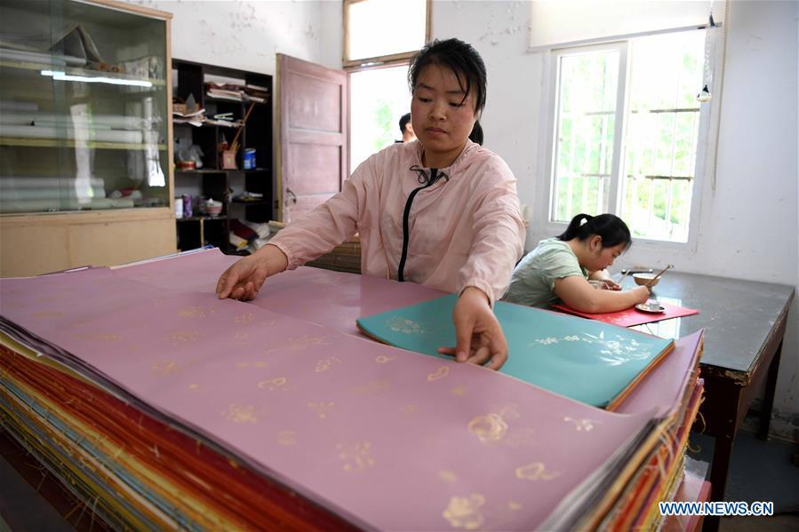 A worker examines half-finished Fenlajian paper at a workshop run by paper artisan Liu Jing in Huanglu Township of Chaohu, east China\'s Anhui Province, May 23, 2019. Fenlajian is a high-end wax mineral paper which dates back to the Tang dynasty (618-907). For centuries, access to the Fenlajian paper had remained a privilege reserved solely for China\'s imperial families, due to the costly materials and the set of complicated procedures involved in its making. The techniques in producing this fine writing and painting material even became lost in the late Qing dynasty (1644-1911), until Liu Jing, an Anhui-based paper artisan, managed to revive them through constant trials by the end of the 20th century. Born in a family of paper-makers, Liu now runs a paper workshop dedicated to making Fenlajian and other classical papers while promoting their know-hows. Liu\'s classical paper processing techniques were listed as a national intangible cultural heritage in 2008, and he himself was named as a national representative inheritor to the aforementioned techniques in 2018. (Xinhua/Liu Junxi)