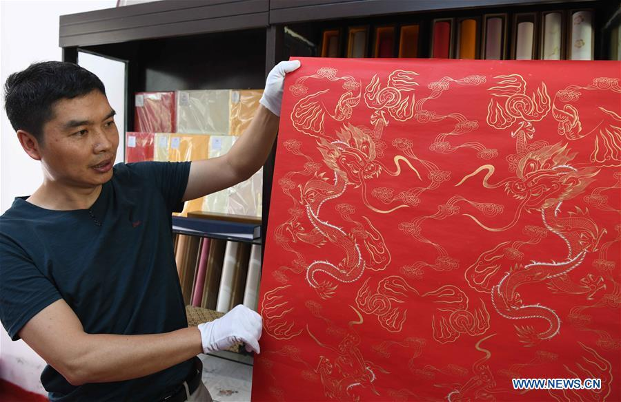 Paper artisan Liu Jing shows a piece of Fenlajian paper at his workshop in Huanglu Township of Chaohu, east China\'s Anhui Province, May 23, 2019. Fenlajian is a high-end wax mineral paper which dates back to the Tang dynasty (618-907). For centuries, access to the Fenlajian paper had remained a privilege reserved solely for China\'s imperial families, due to the costly materials and the set of complicated procedures involved in its making. The techniques in producing this fine writing and painting material even became lost in the late Qing dynasty (1644-1911), until Liu Jing, an Anhui-based paper artisan, managed to revive them through constant trials by the end of the 20th century. Born in a family of paper-makers, Liu now runs a paper workshop dedicated to making Fenlajian and other classical papers while promoting their know-hows. Liu\'s classical paper processing techniques were listed as a national intangible cultural heritage in 2008, and he himself was named as a national representative inheritor to the aforementioned techniques in 2018. (Xinhua/Liu Junxi)