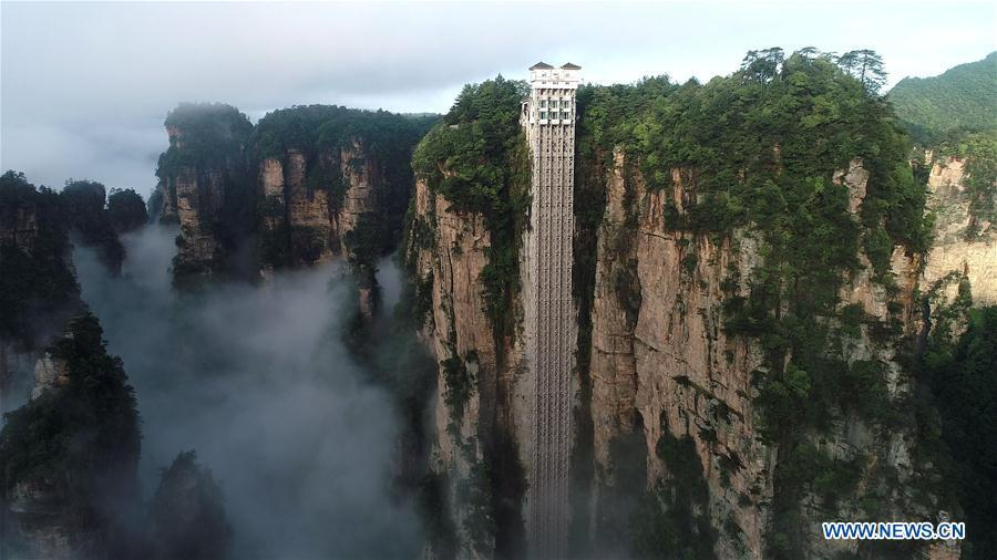 Aerial photo taken on May 25, 2019 shows the 326-meter-high Bailong Elevator, the world\'s highest outdoor elevator, shrouded by fog at the Wulingyuan Scenic Area in Zhangjiajie, central China\'s Hunan Province. (Xinhua/Wu Yongbing)