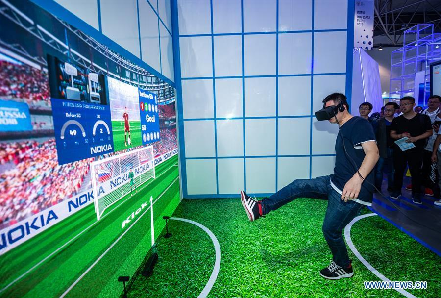 A visitor plays a football game during China International Big Data Industry Expo 2019 in Guiyang, southwest China\'s Guizhou Province, May 26, 2019. The expo on big data opened Sunday in Guizhou Province, focusing on the latest innovation of the technology and its applications. The four-day expo will be attended by 448 enterprises from 59 countries and regions, according to the organizing committee. (Xinhua/Tao Liang)