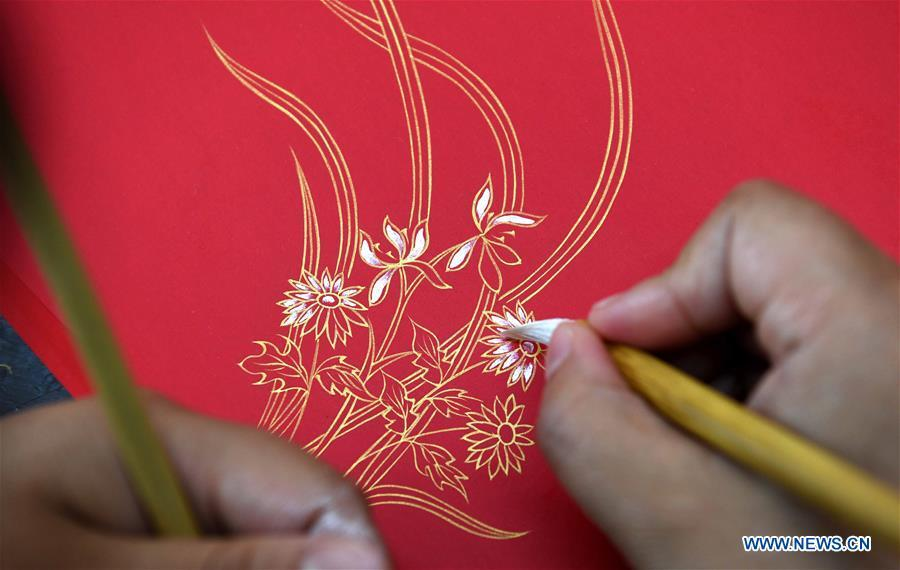 A worker applies gold paint to a piece of Fenlajian paper at a workshop run by paper artisan Liu Jing in Huanglu Township of Chaohu, east China\'s Anhui Province, May 23, 2019. Fenlajian is a high-end wax mineral paper which dates back to the Tang dynasty (618-907). For centuries, access to the Fenlajian paper had remained a privilege reserved solely for China\'s imperial families, due to the costly materials and the set of complicated procedures involved in its making. The techniques in producing this fine writing and painting material even became lost in the late Qing dynasty (1644-1911), until Liu Jing, an Anhui-based paper artisan, managed to revive them through constant trials by the end of the 20th century. Born in a family of paper-makers, Liu now runs a paper workshop dedicated to making Fenlajian and other classical papers while promoting their know-hows. Liu\'s classical paper processing techniques were listed as a national intangible cultural heritage in 2008, and he himself was named as a national representative inheritor to the aforementioned techniques in 2018. (Xinhua/Liu Junxi)