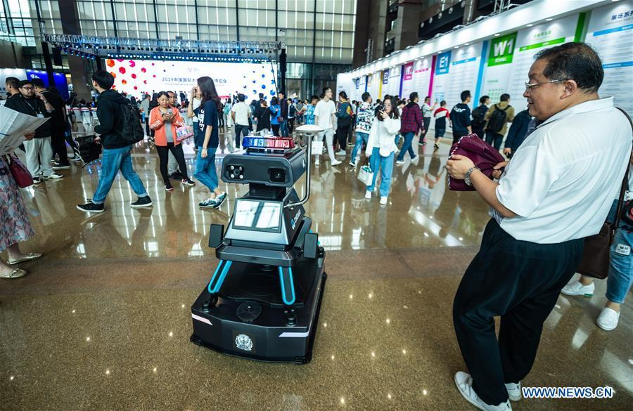 A visitor views an intelligent patrol guard during China International Big Data Industry Expo 2019 in Guiyang, southwest China\'s Guizhou Province, May 26, 2019. The expo on big data opened Sunday in Guizhou Province, focusing on the latest innovation of the technology and its applications. The four-day expo will be attended by 448 enterprises from 59 countries and regions, according to the organizing committee. (Xinhua/Tao Liang)