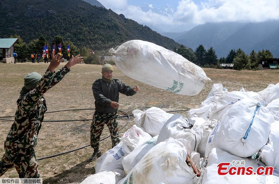 Nepali Army personnel throw bags of waste collected from the Mount Everest at Namche Bazar, on May 27, 2019, before it is transported to Kathmandu to be recycled. Nepal government sent a dedicated clean-up team to Mount Everest this season with a target to bring back 10,000 kilograms of trash in an ambitious plan to clean the world\'s highest rubbish dump. (Photo/Agencies)