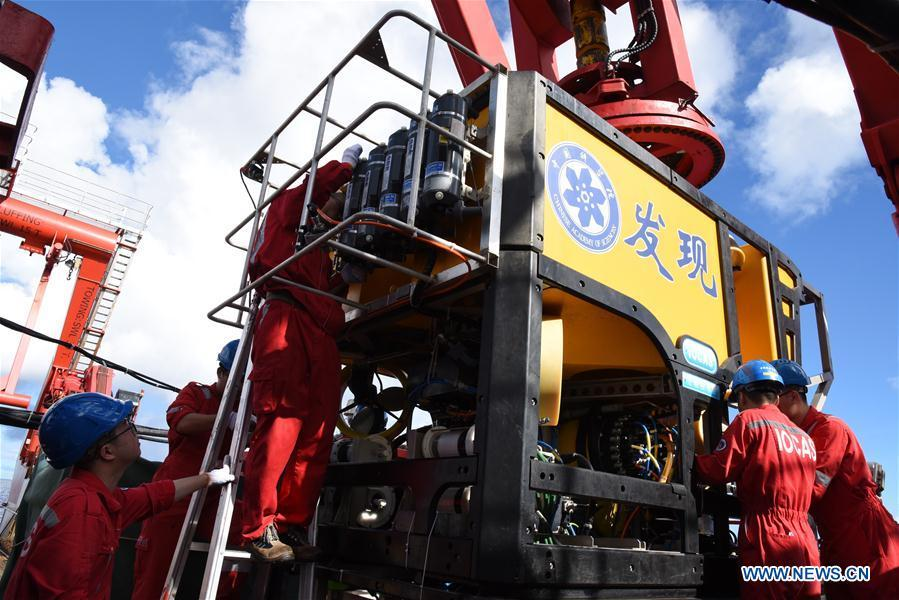 Members of the scientific expedition checks the remote operated vehicle (ROV), Discovery, before it dives into the sea in the south of the Mariana Trench, May 27, 2019. China\'s research vessel KEXUE (Science) on Monday started to explore a series of seamounts in the south of the Mariana Trench, the deepest place of the earth. The remote operated vehicle (ROV), Discovery, dived into the sea on Monday morning to collect videos, information and samples from a small seamount in the southwest of the targeted area. (Xinhua/Zhang Xudong)