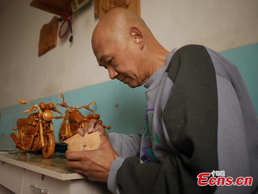 Chuai Mege shows his hand-made miniature motorcycles carved out of wood in Jilin City, Jilin Province. A former automobile mechanic, the 66-year-old man has been fascinated with making miniature motorcycles for 24 years. He said he usually needs a whole year to complete the making a miniature motorcycle because of his attention to detail and quality. For example, he needs to carve over 700 motorcycle parts including  tires, the dashboard, and even screws. (Photo: China News Service/Cang Yan)