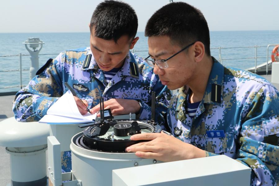 Two cadets are practicing using a nautical tool.  (Photo provided to chinadaily.com.cn)