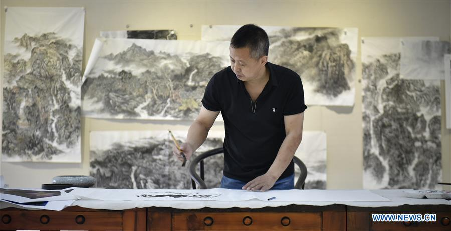 Chen Dongming paints a wood-block painting at his studio in Huanren County of Benxi, northeast China\'s Liaoning Province, May 27, 2019. Chen Dongming, a 52-year-old wood-block painter from Wafang Village of Huanren County in Benxi, learned the techniques from his grandfather since young. As an inheritor of Huanren wood-block painting, a provincial intangible cultural heritage in Liaoning, Chen has been committed to making a proper integration of traditional Chinese landscape paintings and wood-block New Year paintings to promote the craft in an innovative way. (Xinhua/Yao Jianfeng)