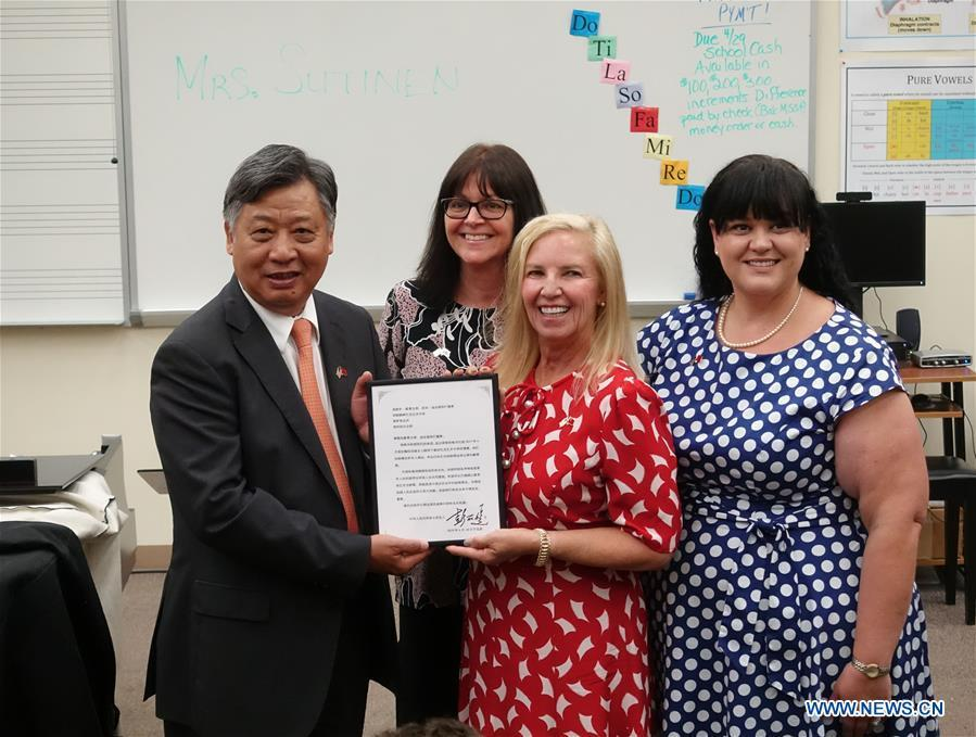 Li Qiangmin, Chinese consul general in Houston (1st L) delivers the letter from Peng Liyuan, wife of Chinese President Xi Jinping, to the faculties of Bak Middle School of the Arts in West Palm Beach, Florida, the United States, April 26, 2019. On April 7, 2017, Peng Liyuan, wife of Chinese President Xi Jinping paid a visit to the school at the invitation of U.S. First Lady Melania Trump, where they watched students perform and talked with them, initiating efforts to build a bridge of people-to-people exchanges between China and the school. Bak\'s School Board Chair Francine Manthy and Executive Director Susy Diaz from the school wrote Peng a letter recently to mark the second anniversary of her visit and again express their appreciation to the Chinese first lady. To their delight, Peng quickly replied. In the letter, Peng said that both China and the United States have a splendid culture, and it is a common wish to strengthen bilateral exchanges, especially among young people. (Xinhua/Liu Jie)
