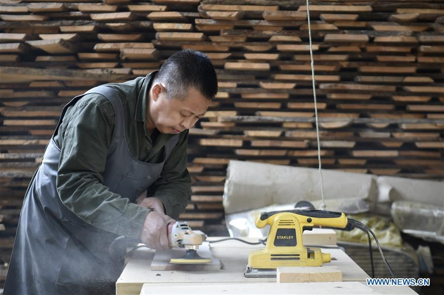 Chen Dongming polishes wood to make wood-block paintings at a factory in Huanren County of Benxi, northeast China\'s Liaoning Province, May 27, 2019. Chen Dongming, a 52-year-old wood-block painter from Wafang Village of Huanren County in Benxi, learned the techniques from his grandfather since young. As an inheritor of Huanren wood-block painting, a provincial intangible cultural heritage in Liaoning, Chen has been committed to making a proper integration of traditional Chinese landscape paintings and wood-block New Year paintings to promote the craft in an innovative way. (Xinhua/Yao Jianfeng)