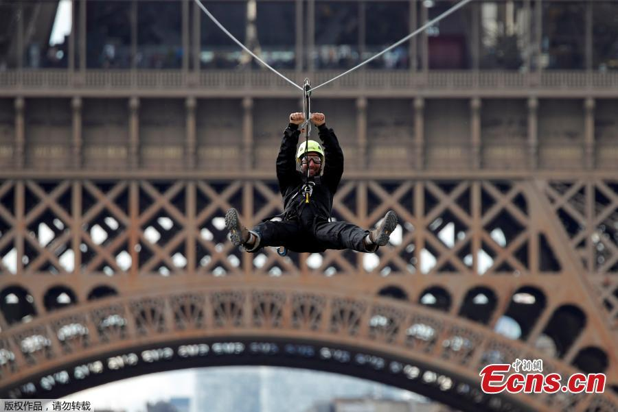 A participant rides a zip line from the second floor of the Eiffel Tower, 115 metres above the ground along an 800-metre long route, as part of the Smash Perrier free event operating until June 2 in Paris, France, May 28, 2019. (Photo/Agencies)