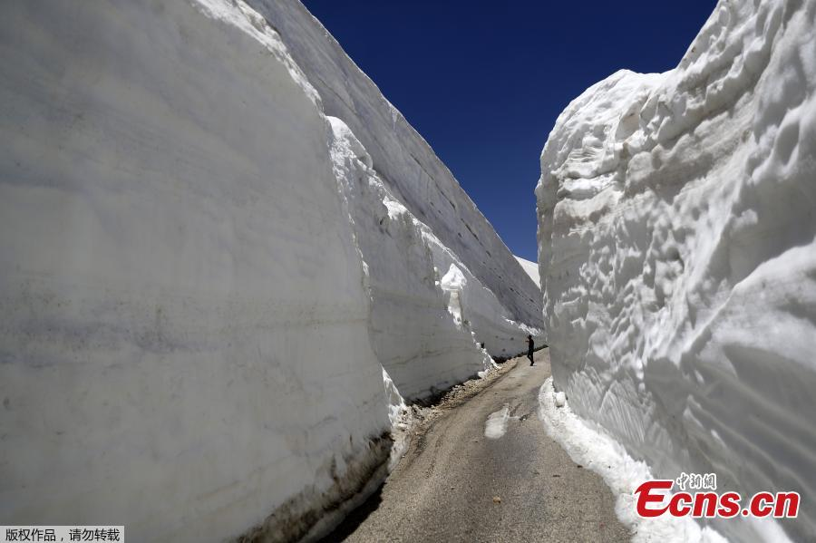 People take pictures on a road, surrounded by walls of snow, on May 28, 2019, in the northern Lebanese village of Ainata al-Arz, 1,620 meters above sea level.(Photo/Agencies)
