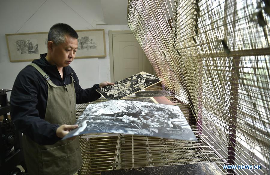 Chen Dongming airs wood-block paintings at his studio in Huanren County of Benxi, northeast China\'s Liaoning Province, May 27, 2019. Chen Dongming, a 52-year-old wood-block painter from Wafang Village of Huanren County in Benxi, learned the techniques from his grandfather since young. As an inheritor of Huanren wood-block painting, a provincial intangible cultural heritage in Liaoning, Chen has been committed to making a proper integration of traditional Chinese landscape paintings and wood-block New Year paintings to promote the craft in an innovative way. (Xinhua/Yao Jianfeng)