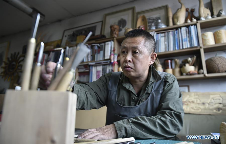 Chen Dongming chooses tools to make a wood-block painting at his studio in Huanren County of Benxi, northeast China\'s Liaoning Province, May 27, 2019. Chen Dongming, a 52-year-old wood-block painter from Wafang Village of Huanren County in Benxi, learned the techniques from his grandfather since young. As an inheritor of Huanren wood-block painting, a provincial intangible cultural heritage in Liaoning, Chen has been committed to making a proper integration of traditional Chinese landscape paintings and wood-block New Year paintings to promote the craft in an innovative way. (Xinhua/Yao Jianfeng)