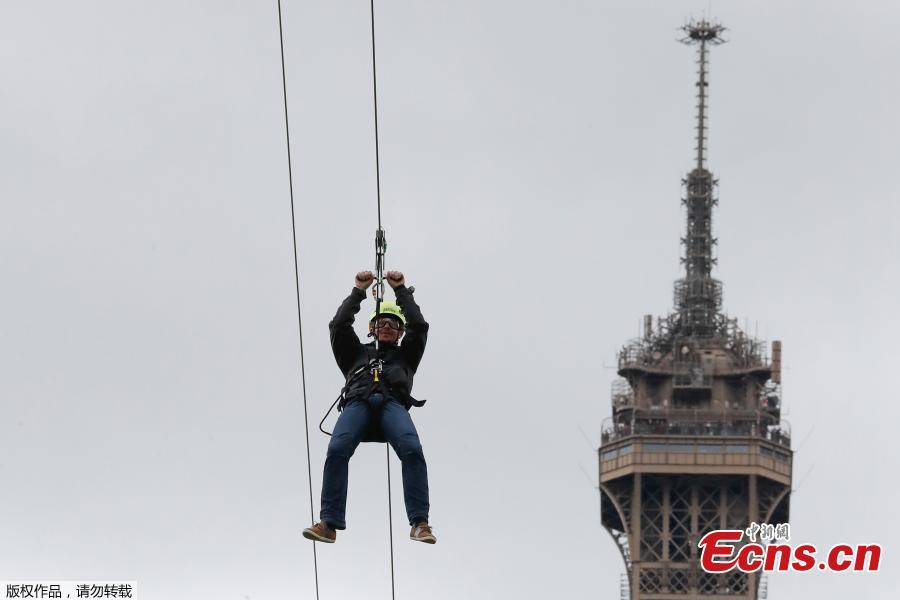 A person rides on a zip-line descending from the second floor of the Eiffel Tower on May 28, 2019 in Paris. The 800 meter crossing takes one minute at a speed of 90km/h. The zip-line will be opened from May 29 to June 2, 2019. (Photo/Agencies)