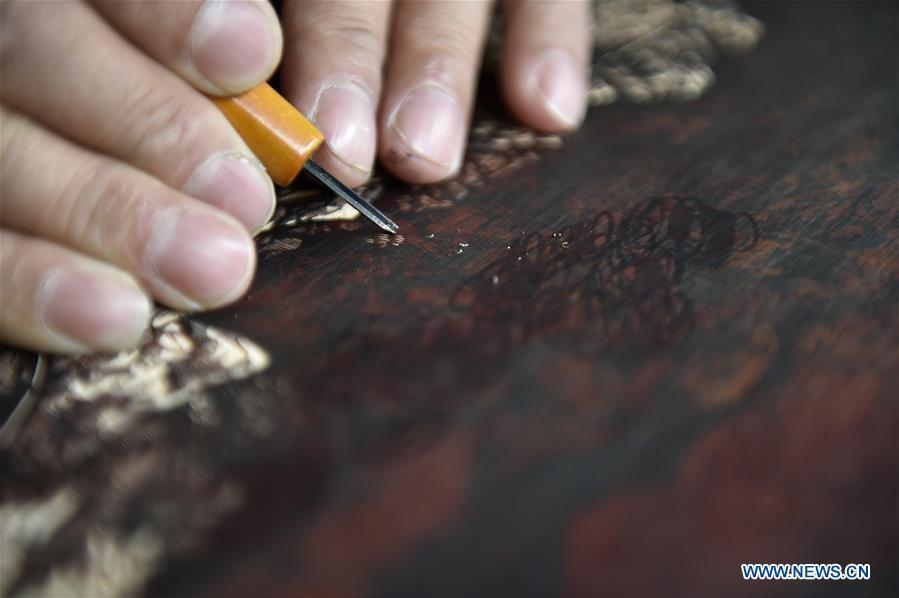 Chen Dongming works on a wood-block painting at his studio in Huanren County of Benxi, northeast China\'s Liaoning Province, May 27, 2019. Chen Dongming, a 52-year-old wood-block painter from Wafang Village of Huanren County in Benxi, learned the techniques from his grandfather since young. As an inheritor of Huanren wood-block painting, a provincial intangible cultural heritage in Liaoning, Chen has been committed to making a proper integration of traditional Chinese landscape paintings and wood-block New Year paintings to promote the craft in an innovative way. (Xinhua/Yao Jianfeng)