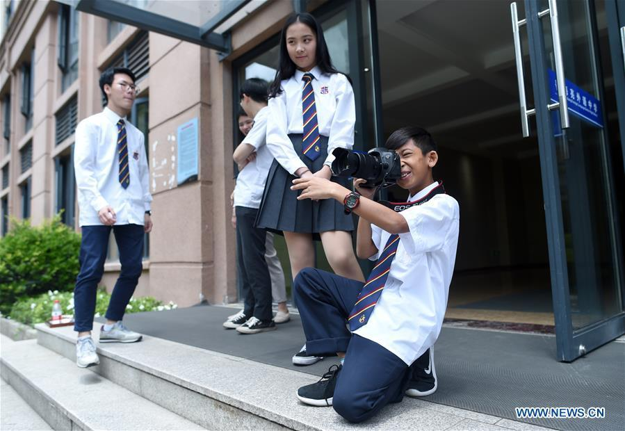 Thuch Salik takes pictures for classmates at a foreign language school in Zhuji, east China\'s Zhejiang Province, May 29, 2019. Thuch Salik became viral overnight when a video clip showing him selling souvenirs in a dozen distinct languages near Angkor Wat was shared online on November 2018. Born in a family with financial difficulties, the 14-year-old Cambodian boy got global attention for his multilingual talent. In May, Salik was offered a place at a foreign language school in Zhuji of east China\'s Zhejiang Province on an education programme funded by a private sponsor in China. Salik said he has high expectations for his education opportunity and life in China. (Xinhua/Han Chuanhao)