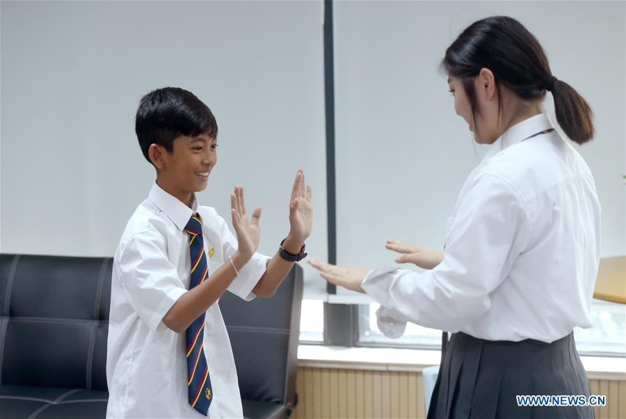 Thuch Salik (L) plays a game with a classmate at a foreign language school in Zhuji, east China\'s Zhejiang Province, May 29, 2019. Thuch Salik became viral overnight when a video clip showing him selling souvenirs in a dozen distinct languages near Angkor Wat was shared online on November 2018. Born in a family with financial difficulties, the 14-year-old Cambodian boy got global attention for his multilingual talent. In May, Salik was offered a place at a foreign language school in Zhuji of east China\'s Zhejiang Province on an education programme funded by a private sponsor in China. Salik said he has high expectations for his education opportunity and life in China. (Xinhua/Han Chuanhao)