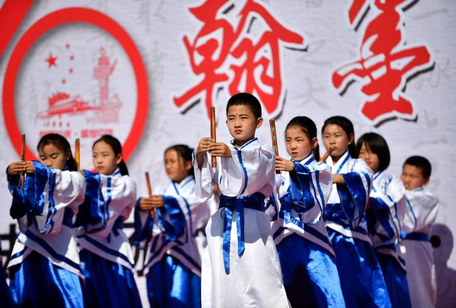 Primary school students wearing traditional Han Chinese attend a ceremony during a calligraphy competition in Yinchuan, capital of Northwest China\'s Ningxia Hui autonomous region, on Tuesday.  (Photo by Li Jing/for chinadaily.com.cn)