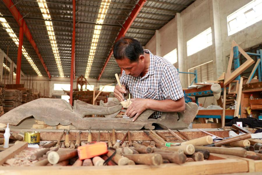 A craftsman repairs a wooden component from an ancient residence in the warehouse of Bengbu Ancient Residence Exhibition Park based in Bengbu, East China\'s Anhui province, on May 28, 2019. (By Zhu Lixin/chinadaily.com.cn)
