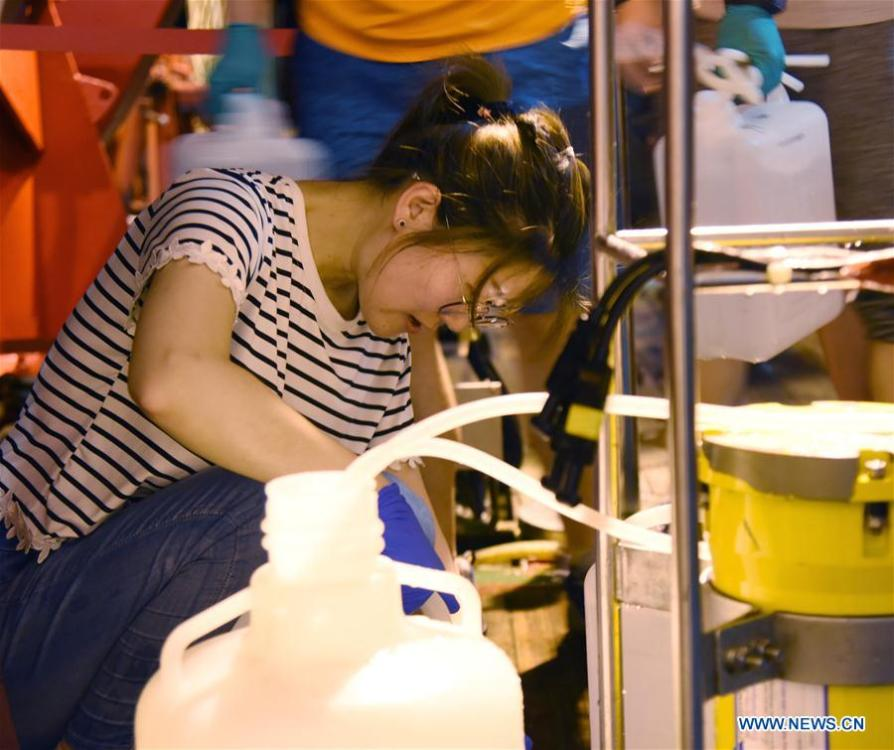 A researcher collects samples of sea water from the CTD(Conductivity Temperature Depth) on China\'s research vessel KEXUE(Science) in the western Pacific Ocean, May 29, 2019. KEXUE is carrying out a 20-day long investigation over a series of seamounts in the south of the Mariana Trench in the western Pacific Ocean. They will focus on biological diversities, ecological systems and biological distributions of the seamounts that they planned to explore. (Xinhua/Zhang Xudong)
