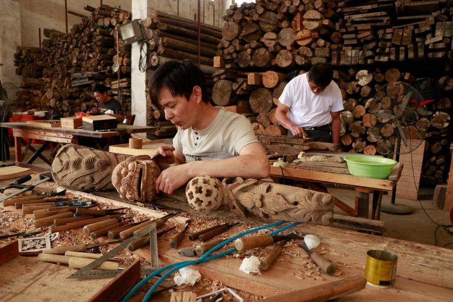 Craftsmen repair wooden components of ancient residences in the warehouse of Bengbu Ancient Residence Exhibition Park, based in Bengbu city of East China\'s Anhui province. (By Zhu Lixin/chinadaily.com.cn)