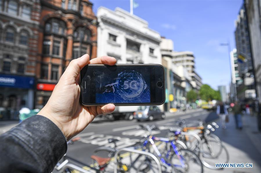 Photo taken on May 30, 2019 shows A 5G network logo on the screen of a mobile phone in London, Britain. Mobile network operator EE said on last Wednesday that it would launch Britain\'s first 5G service in six major cities on May 30th. (Xinhua/Alberto Pezzali)