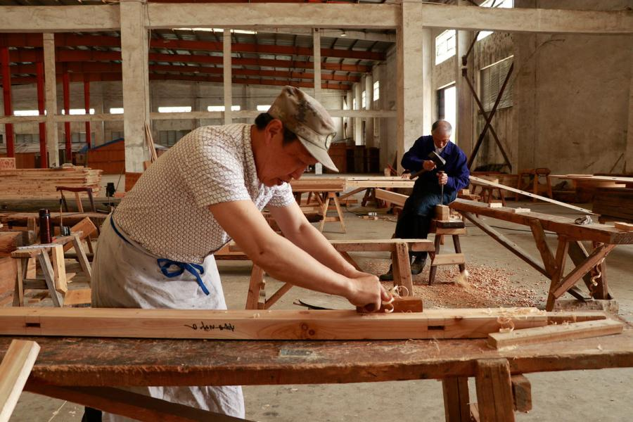 Two carpenters work on new wooden components for repairing ancient residences in the warehouse of Bengbu Ancient Residence Exhibition Park, based in Bengbu city of East China\'s Anhui province. (By Zhu Lixin/chinadaily.com.cn)