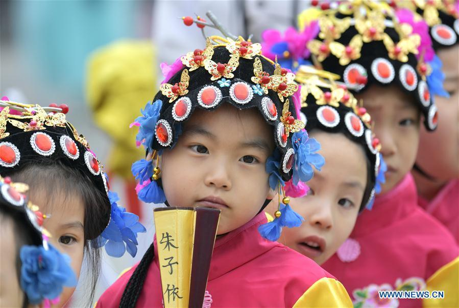 Children wait to perform during an event in celebration of the International Children\'s Day in Xuanen County of Enshi Tujia and Miao Autonomous Prefecture, central China\'s Hubei Province, May 30, 2019. (Xinhua/Song Wen)